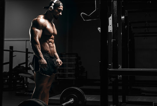 Muscular athletic bodybuilder man hard workout  in gym over dark background with dramatic light with barbell