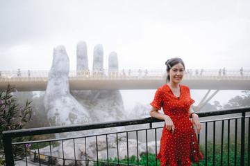 Asian woman take picture with beautiful view of Golden Bridge. Golden Bridge is lifted by two giant hands in the tourist resort on Ba Na Hill in Da Nang, Vietnam.