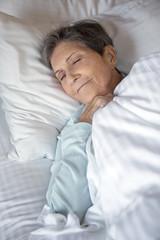 Elderly woman getting a good nights rest.