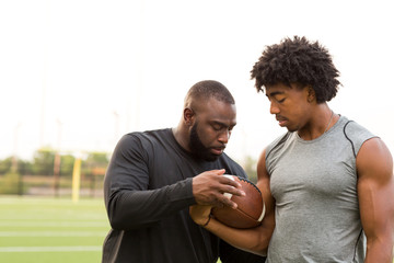 American Football coach training a young athlete.
