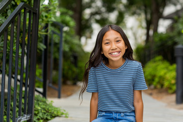 Portrait of a young Asian girl smiling outside.