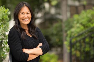 Portrait of an Asian woman sitting outside.