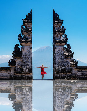 Woman traveler standing at the ancient gates of Pura Luhur Lempuyang temple aka Gates of Heaven in Bali, Indonesia