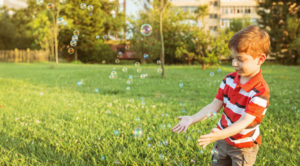 Happy cute boy playing to catch soap bubbles in the park