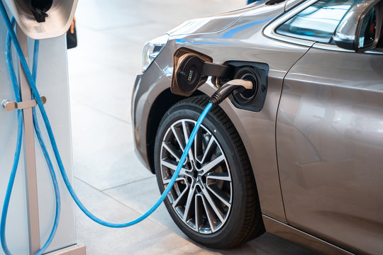 Power supply plugged into an electric car being charged.