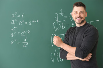 Handsome math teacher writing on blackboard in classroom