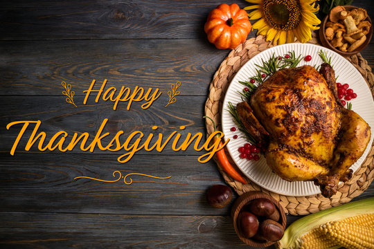Happy Thanksgiving holiday background. Roasted whole chicken or turkey with autumn vegetables for thanksgiving dinner on wooden background