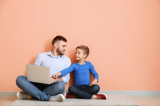 Father and his little son with laptop sitting near color wall