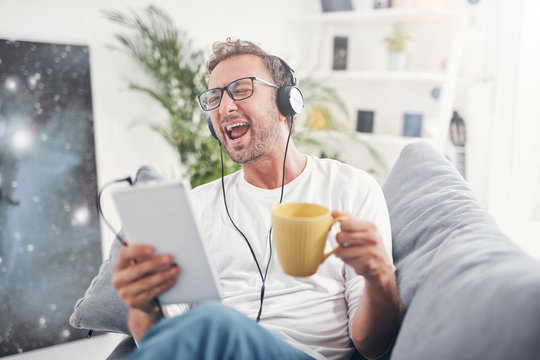 Man listening to music and using tablet in the living room.