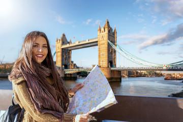 Photo sur Plexiglas Londres Attraktive Touristin mit Stadtplan in der Hand steht vor der Tower Brücke in London während eines Städtetrips