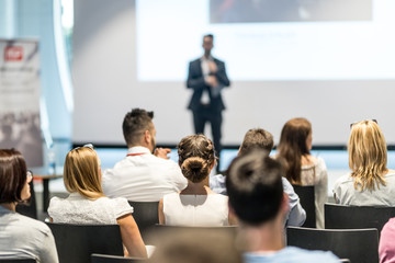 Wall Mural - Male speaker giving a talk in conference hall at business event. Audience at the conference hall. Business and Entrepreneurship concept. Focus on unrecognizable people in audience.