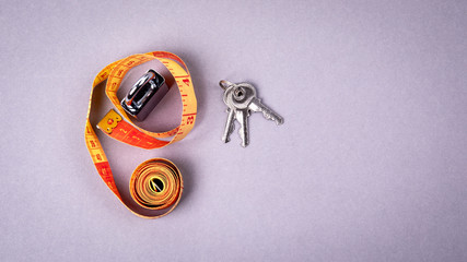 Measure tape and padlock key on a gray background. Weight watching, healthy lifestyle and fitness concept. Space for text and picture