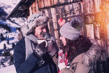 verliebtes Paar mit Glühwein vor Skihütte in den Bergen