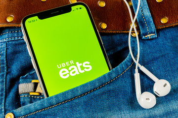 Sankt-Petersburg, Russia, April 14, 2018: Uber Eats application icon on Apple iPhone X smartphone screen close-up in jeans pocket. Uber eats app icon. Social network. Social media icon