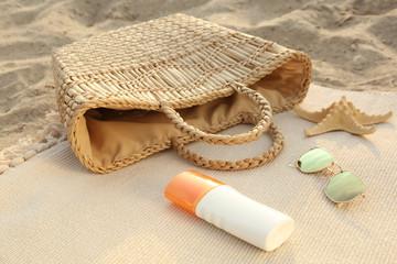 Bag with sunscreen cream, sunglasses and starfish on sand beach