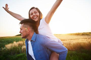 Happy man carrying girlfriend on his shoulders