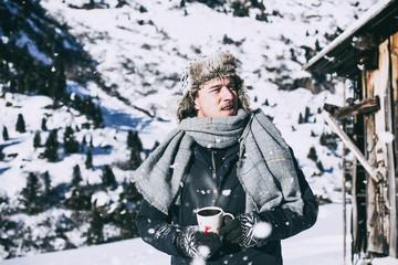 Mann mit Tasse und Schal und Mütze in den Alpen im Urlaub