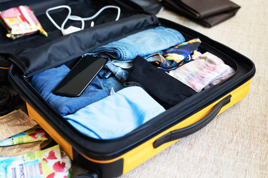 An open suitcase with men's clothing, packed for a business trip or travel