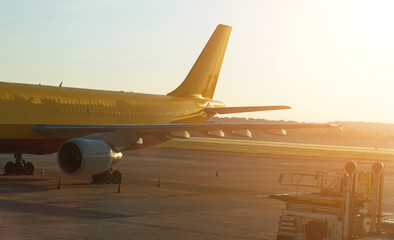 Cargo airplane on the runway at sunset. Wall mural