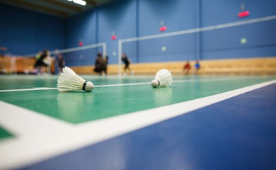 Badminton - badminton courts with players competing; shuttlecocks in the foreground (shallow DOF; color toned image).