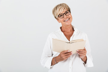Portrait of joyous middle-aged woman wearing eyeglasses reading book