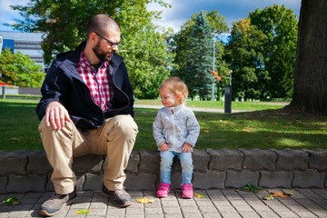 girl and her father sitting on a sidewalk