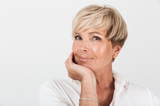 Portrait closeup of middle-aged woman with short blond hair looking at camera
