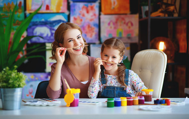 mother and child daughter painting draws in creativity in kindergarten.