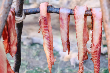 Pieces of jerky over the fire are prepared. Meat cut into strips is strung on branches and cooked on fire.