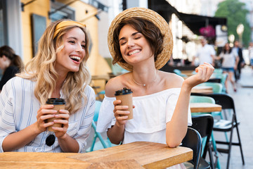 Obraz Happy young positive optimistic girls friends sitting outdoors in cafe drinking coffee talking with each other. - fototapety do salonu