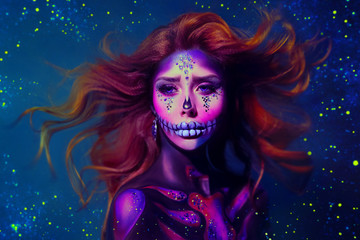 Redhead woman with creative make-up in the style of a sugar skull. Hair flies and waves against a cold, blue background of space, stars, radiance and sparkles. Free space for text. Art retouch photo