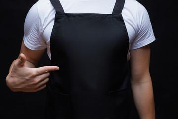 Closeup strong man wearing black apron.