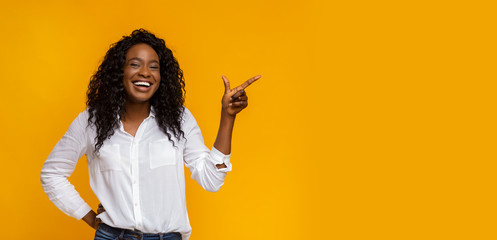 Cheerful black girl pointing at empty space Wall mural