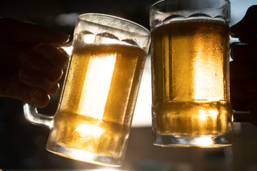 Closeup toast clinking fresh lager beer glasses mugs with sun rays in hot summer day