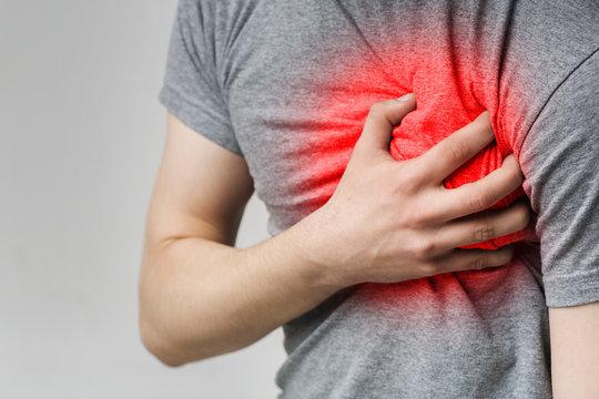 Caucasian man having heart ache, holding hand on chest