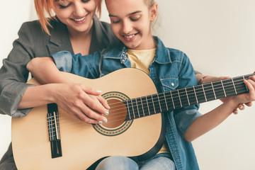 Smiling woman teaching girl to play guitar