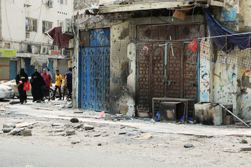 Yemeni people walk past shops damaged during clashes between separatists and government forces in Aden