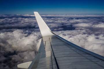 Window wing view of airplane flying on high altitude, above a bed of puffy clouds. Day view inside commercial plane window of a metal wing, without carrier logo.