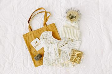 Wall Mural - Knitted white sweater with  tote bag and christmas decorations. Winter fashion clothes collage on white background. Top view flat lay. .