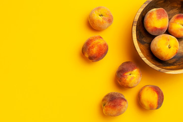 Wall Mural - Flat lay composition with peaches. Ripe juicy peaches in wooden bowl on yellow background. Flat lay, top view, copy space. Fresh organic fruit, vegan food. Harvest concept