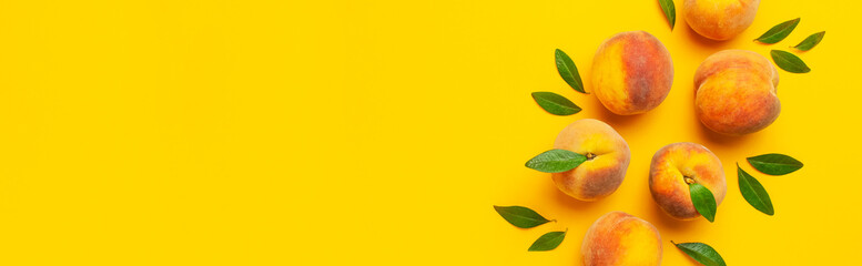 Wall Mural - Flat lay composition with peaches. Ripe juicy peaches with green leaves on yellow background. Flat lay, top view, copy space. Fresh organic fruit, vegan food. Harvest concept