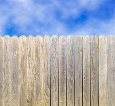Whitewashed rustic wood privacy fence with blue sky and clouds