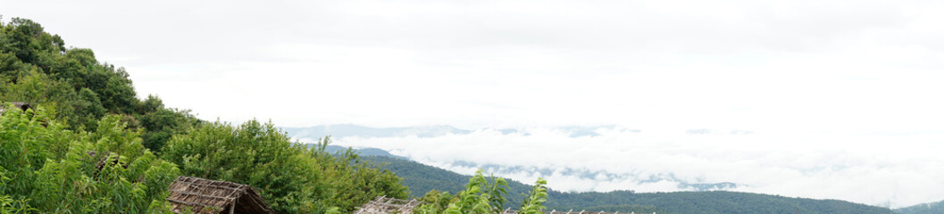 panoramic view of mountains and the abstract fog on the sky, forested mountain slope in low lying cloud with the wooden bamboo hut.