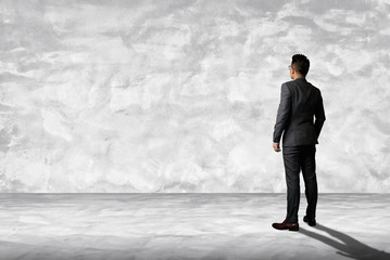 the abstract image of the businessman standing in the white empty room and copy space. the concept of business, commercial, advertising and template.