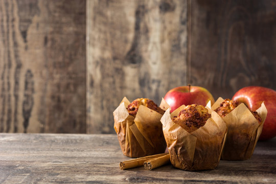 Apples and cinnamon muffins on wooden table. Copyspace