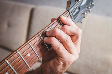 F chord - close-up male Caucasian hand takes a chord on a 6 string guitar