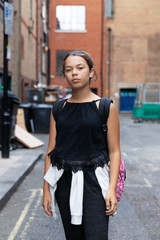 Portrait of a young girl in an alley full of garbage