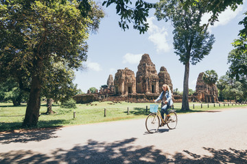 Young woman riding bicycle next to Pre Rup temple in Angkor Wat complex, Cambodia