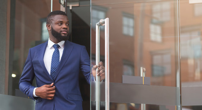 Handsome african american ceo leaving business center after meeting