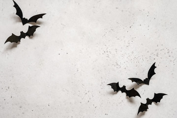 halloween decoration concept - black bats on white concrete background